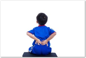 Back pain. Athlete little asian (thai) boy in blue sportswear sitting and rubbing the muscles of his lower back, cropped torso portrait, isolated on white background. Studio shot