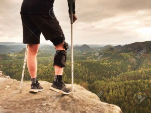 80047051-man-with-a-crutches-and-broken-leg-fixed-in-knee-brace-feature-traveler-with-hurt-leg-in-bandages-st-Stock-Photo